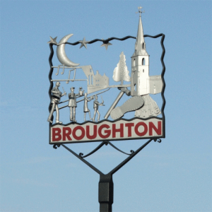 Broughton village sign, featuring its tin can band on Tanders